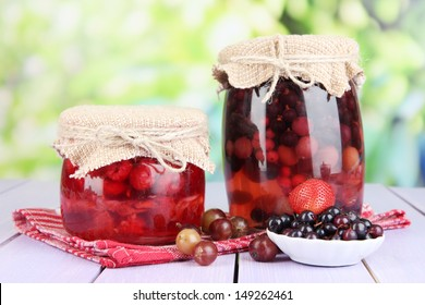 Home made berry jam on wooden table on bright background