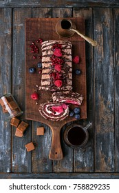 Home made 'Black Forest' roll cake Buche de Noel decorated with berries and served with Coffee. Top view