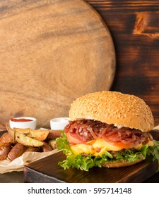 Home made burger with caramelized onion and cheese served with potato wedges, copy space