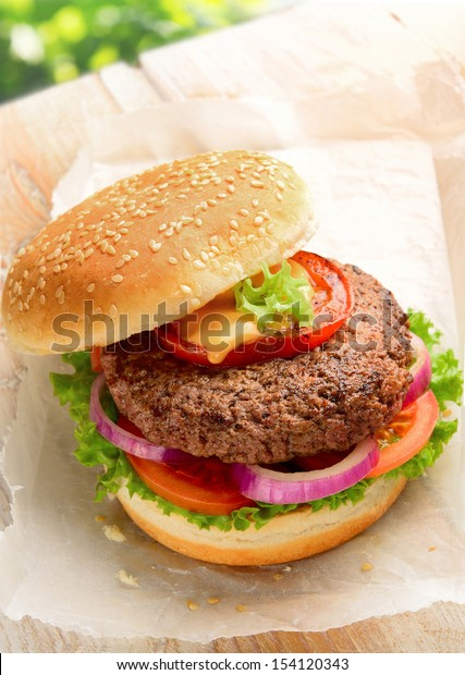 Home made burger made with pure ground beef. Garnished with red onion, tomato and lettuce on a hamburger bun, topped with sesame seeds.