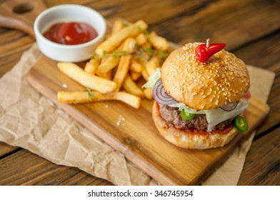 Home made burgers on wooden background with sauce