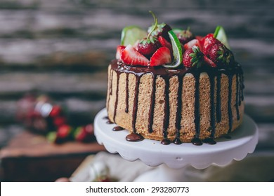 Home made cake/cheesecake decorated with strawberries, lime and chocolate