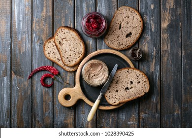 Home made chicken liver pate or paste served with home made bread and cranberry sauce with chilies over a rustic wooden board. Top view