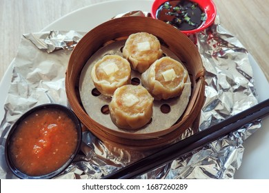 Home made chinese dimsum served on the traditional steamer decorated with alumunium foil, sweet chili sauce and ketchup. Top View