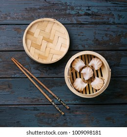 Home made chinese dumplings served on the traditional steamer over blue wooden background. Top View. Square image