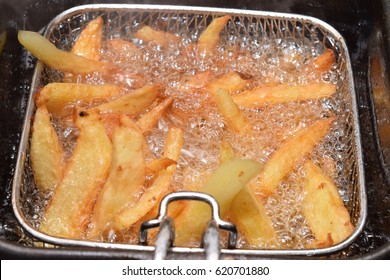 Home made chips in a hot deep fryer with boiling oil