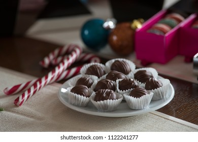 Home made chocolate pralines for family holidays on a plate on wooden table next to candy canes