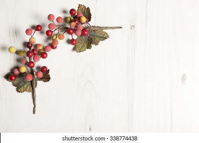 Home made colourful holly and berries on a light wooden surface