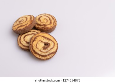 Home made cookies of eliptical shape, made with chocolate, butter and vanilla, isolated on white background, soft light, angle view, copy space