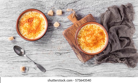 Home made creme brulee served with brown sugar cubes on grey wooden background with grey napkin. Top view with space on left