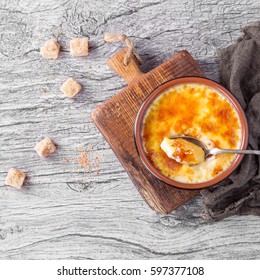 Home made creme brulee served with brown sugar cubes on grey wooden background with grey napkin. Top view with space on left. Square image
