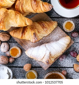 Home Made Croissant served with honey, jam, nuts, grapes and black tea over a rustic wooden board. Top View. Square image