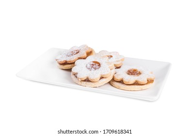 Home made flower shaped cookies with peach jam on white plate with powder sugar isolated on white