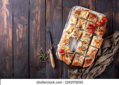 Home made focaccia flat bread cut into pieces served with baked tomatoes, sea salt and fresh rosemary, with vintage napkin and knife over a wooden background. Top View