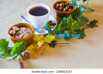 Home made fresh acorn coffee in a white cup with acorns and oak leafs decoration. Acorns contain a lot of tannin. A common drink for bad times during world war 2 in Europe. Food trend. Selective focus