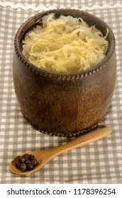 home made fresh sauerkraut in a wood barrel and spoon with juniper berries