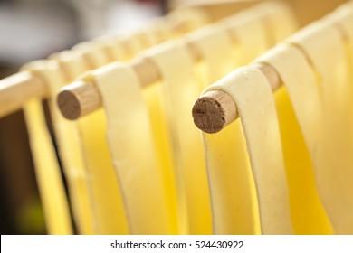 Home made fresh semolina pasta drying on an Italian wooden rack