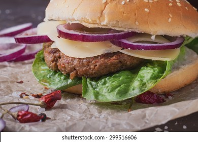 Home made freshly cooked burger with seasoning, vegetables and greens