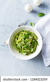 Home made fusilli pasta with arugula-basil pesto, parmesan and basil leaves. Flat lay. Mediterranean cuisine