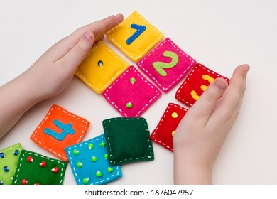 Home made game: find the right pair. Different color stuffed felt square with numbers and matching domino style dots. Early education, learning numbers.