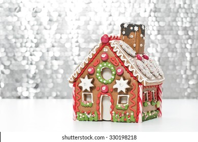 home made gingerbread house with a silver background