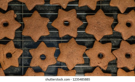 Home made gingerbread star shaped cookies on a cooling wire rack. Baking for Christmas concept.