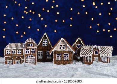 home made gingerbread town with bokeh sky out of blue velvet and christmas lights as advent decoration for the family