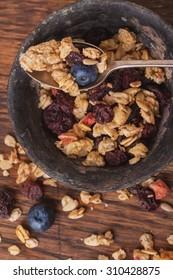 Home Made Granola breakfast with white plain yogurt, blueberries, raspberries and dry cherries on rustic wooden background