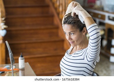 Home made hair dye at home for beauty young caucasian woman looking at the mirror - stay at home concept for coronavirus emergency worldwide pandemic contagion