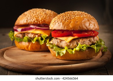 Home made hamburger with beef, onion, tomato, lettuce and cheese. Fresh burger closeup on wooden rustic table with potato fries and chips.