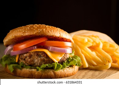 Home made hamburger with beef, onion, tomato, lettuce and cheese. Fresh burger closeup on wooden rustic table with potato fries, beer and chips. Cheeseburger.