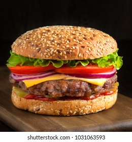 Home made hamburger with lettuce and cheese on board.