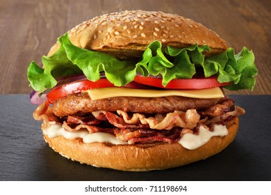Home made hamburger with lettuce, cheese and bacon. Fast food.
