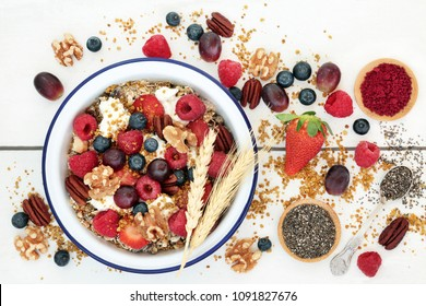 Home made healthy breakfast super food concept with granola, yoghurt,  fruit, nuts, chia seeds, pollen grain & acai berry powder. High in omega 3, protein, anthocyanins, antioxidants & dietary fibre.