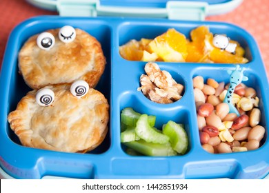 Home made healthy kids lunch box! Vegan pies, orange, celery, walnut and bean salad.