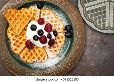 Home made heart shaped waffles served with greek yogurt and frozen berries and a dusting of icing sugar. A delicious breakfast treat.