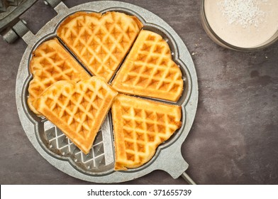 Home made heart shaped waffles served in a traditional cast iron waffle pan with a healthy peanut butter banana smoothie milkshake.