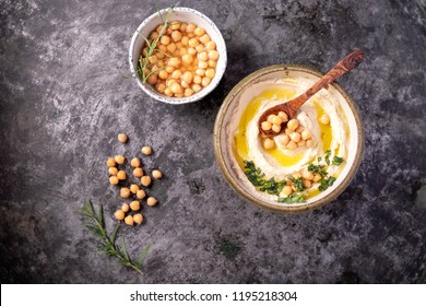 Home made hummus bowl, decorated with boiled chickpeas, herbs and olive oil over a rustic metal background. Top View.