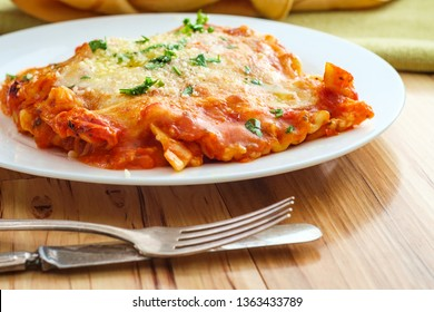 Home made Italian baked cheese lasagna on wooden kitchen table