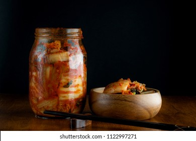 Home made kimchi on jar and wooden bowl with black background