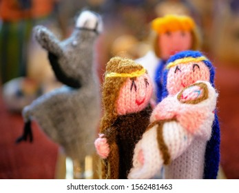 Home made knitted nativity set with Mary, Joseph and Jesus with angel gabriel and donkey in the background