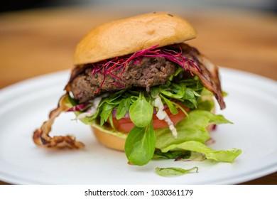 Home made lamb hamburger with fresh vegetables and bacon