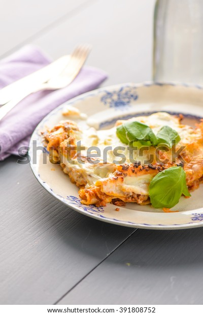 Home made lasange on a plate and some basil on the top