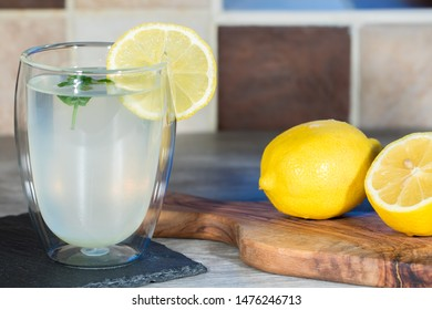 Home made lemonade. Refreshing healthy glass of cold water with lemon. Fresh lemons and mint with authentic summer drink.