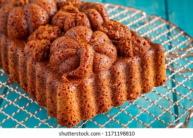 Home made loaf of pecan pumpkin bread baked in decorative fall themed pan sitting on copper cooling rack on blue wooden table