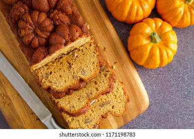 Home made loaf of pumpkin bread sitting on wooden cutting board with knife shot from above
