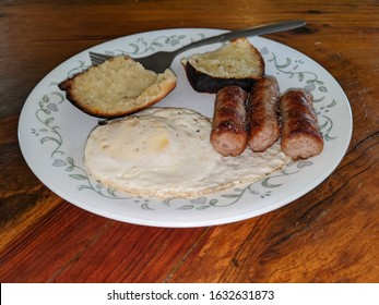 A home made morning breakfast plate with a semi burnt buttered roll an egg soft over easy and three sausage links on a ceramic plate with a fork on a wooden table top