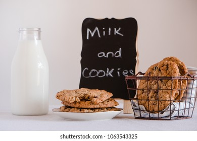 Home made oatmeal cookies with a sign and bottle of milk.