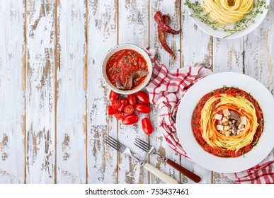 Home made pasta alla Arrabiata served with Marinara sauce decorated with parmesan cheese, anchovies, chili and thyme over a rustic wooden board. Top View. Copy space