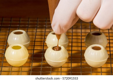 Home made patisserie: A delicious truffle ganache is being filled into white chocolate praline molds.